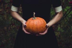 Woman's hands hold a pumpkin