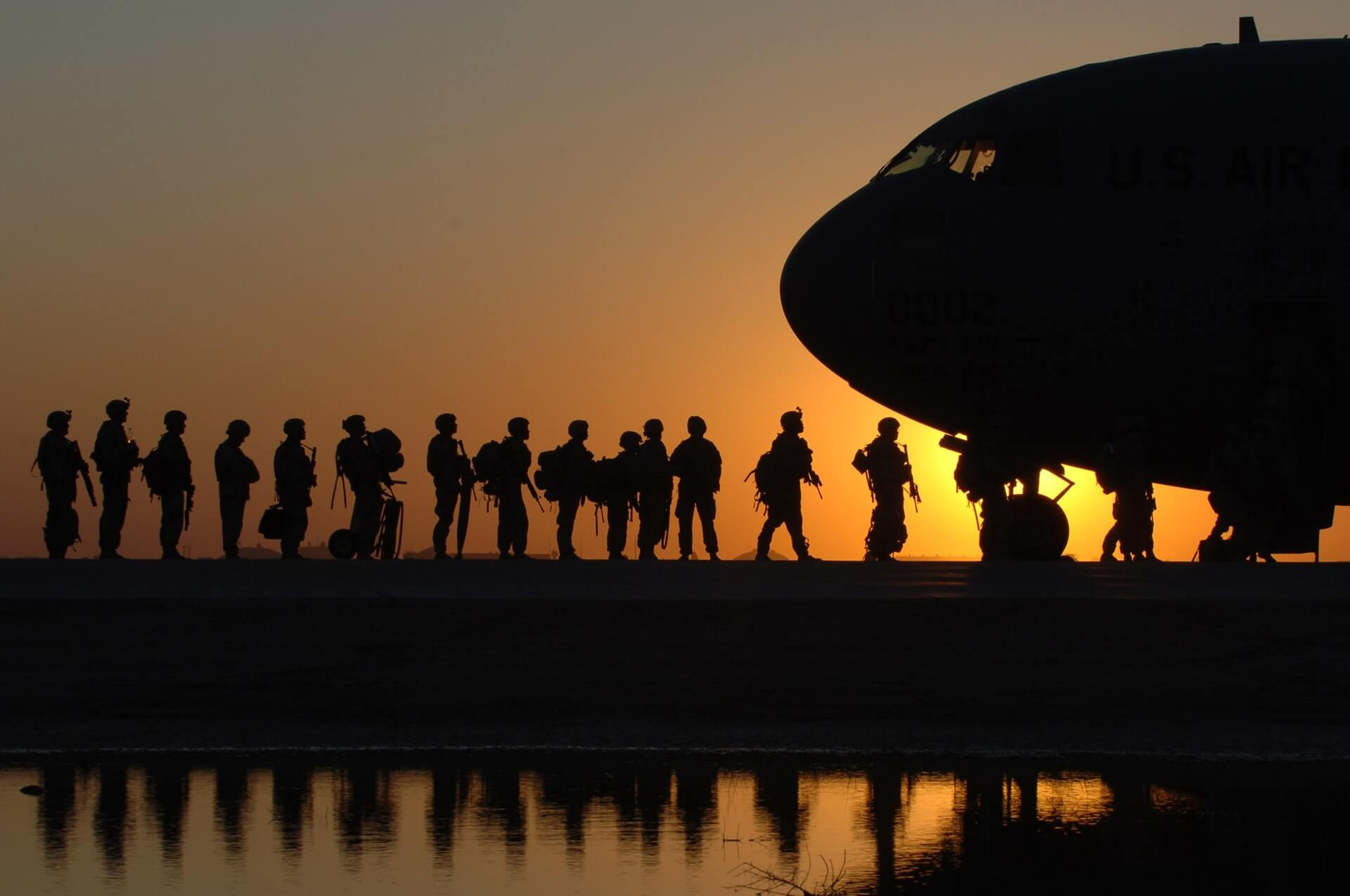 Soldiers silhouetted agains the dawn sky line up to board a military plane.