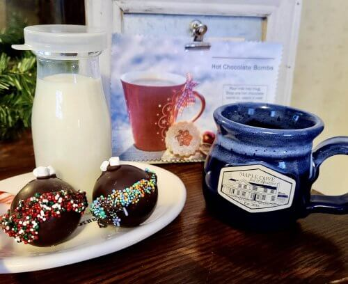"""Hot chocolate """"bombs"""" on a plate next to mugs and milk"""