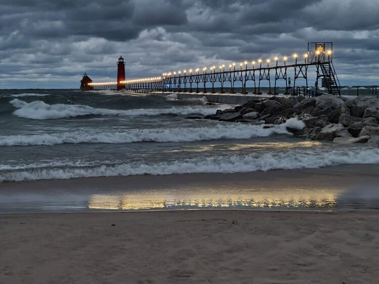 Grand Haven Inner and Outer Pier Lights with the white lights of the catwalk reflecting in the waves and pre-dawn storm clouds in background