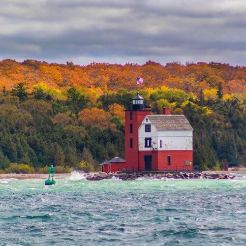 Round Island Lighthouse with fall-colored trees on Bois Blanc Island in background