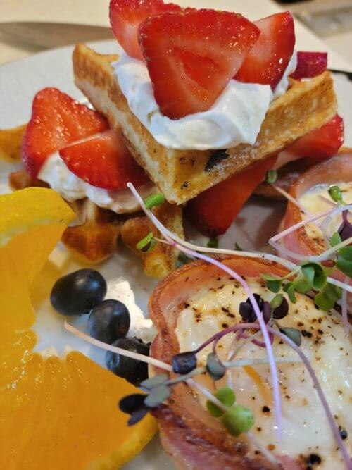 Strawberry shortcake waffles plus bacon-wrapped eggs topped with micro greens