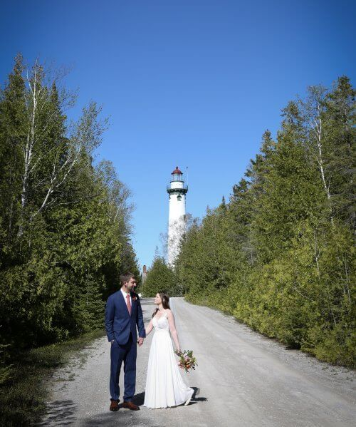 Bride and groom walking with New Presque Isle Lighthouse in the background