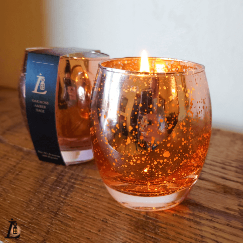 In a glass container, candles made for Lamplighter B&B.