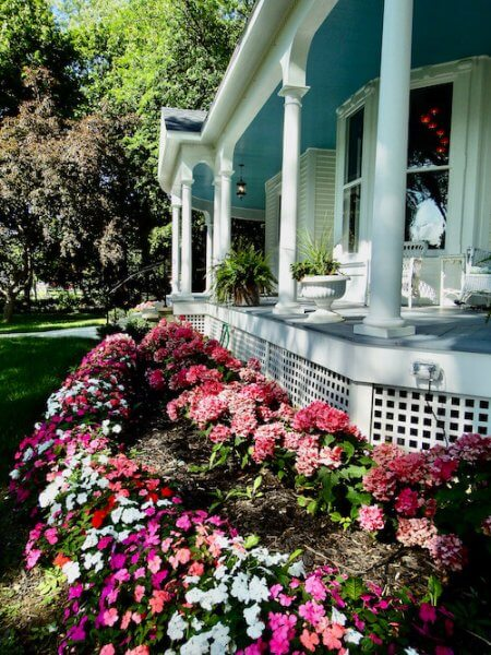 Abundant summer flowers in front of a section of the porch